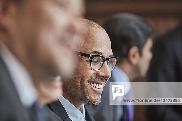 Smiling businessman sitting with his colleagues