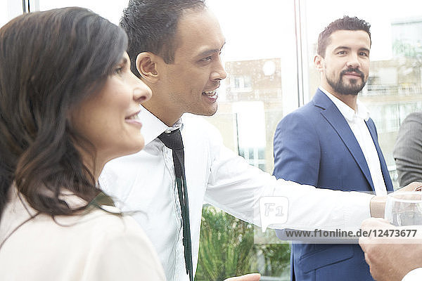 Businesspeople smiling at toasting by a window