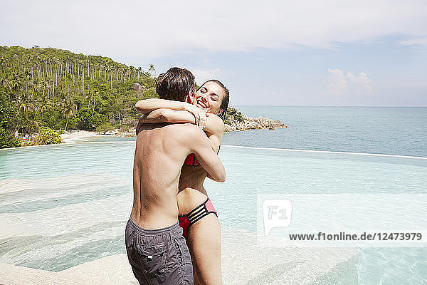 Young couple embracing beside swimming pool in Ko Samui  Thailand