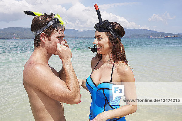 Young couple with snorkels at beach