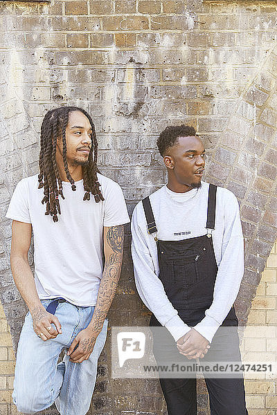 Young men against brick wall