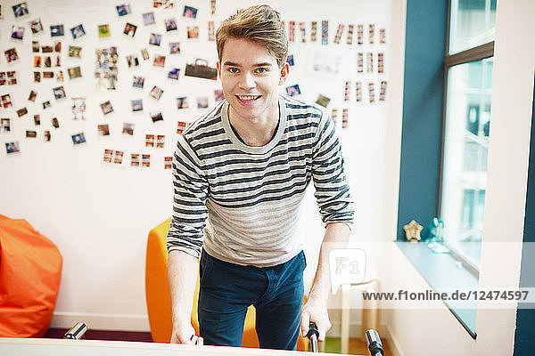 Young businessman playing table football in office break room
