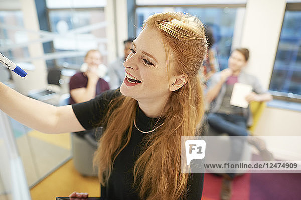 Young businesswoman writing on whiteboard during meeting