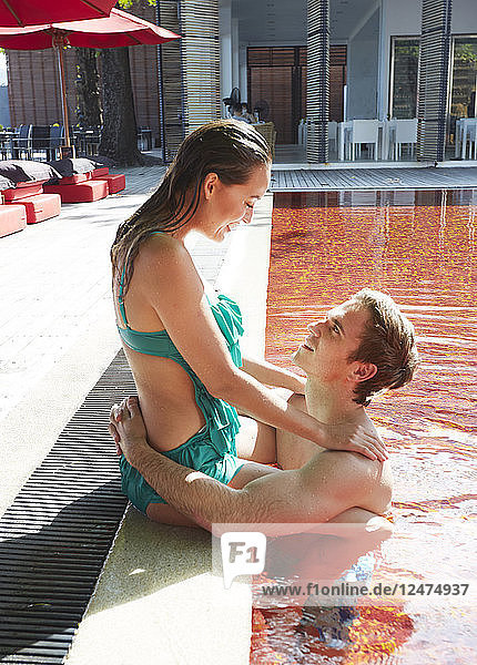 Young couple embracing at red swimming pool