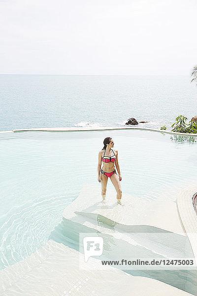 Young woman wearing red bikini in swimming pool