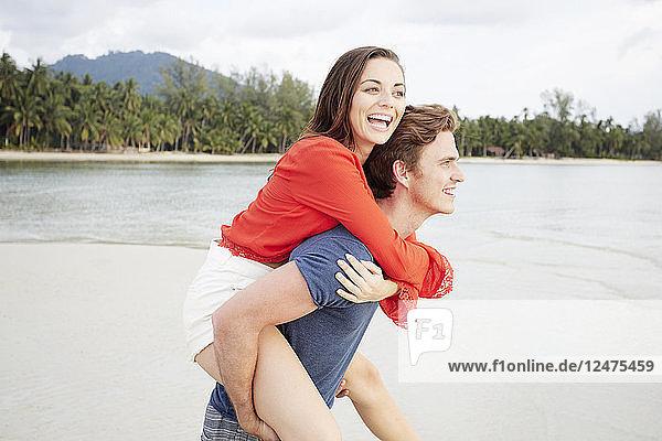 Young man giving girlfriend piggyback at beach in Ko Samui  Thailand