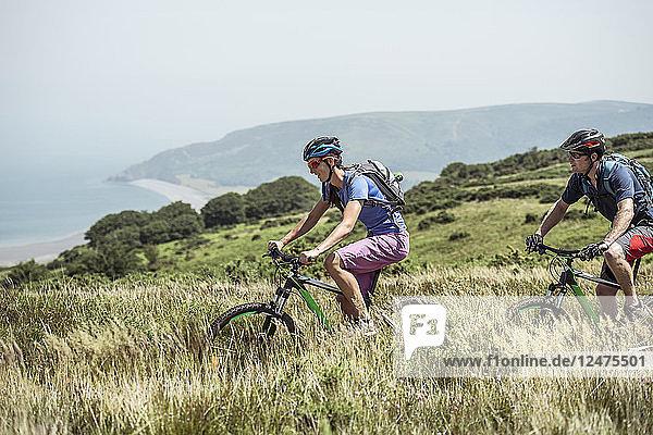 Couple mountain biking on hill in Porlock Weir  England