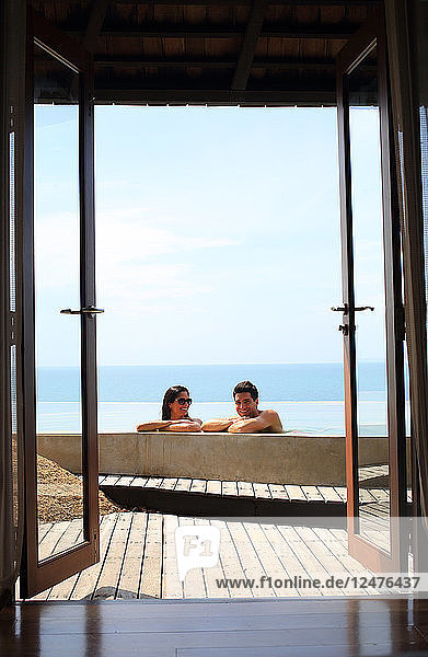 Young couple in swimming pool behind open glass doors
