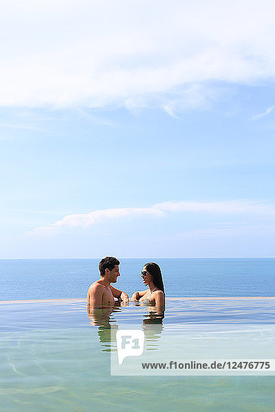 Young couple in swimming pool by sea
