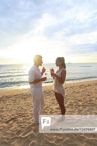Young couple holding drinks on beach