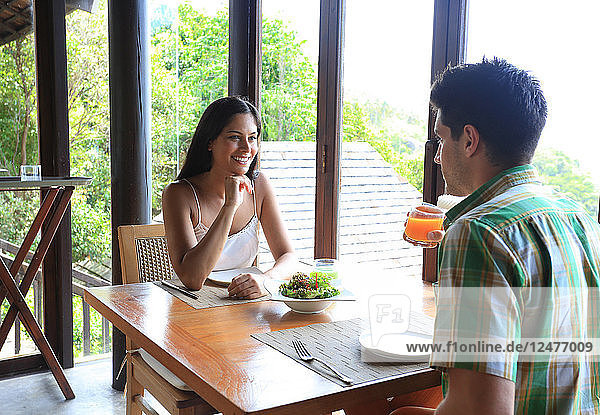 Young couple sitting at table with salad