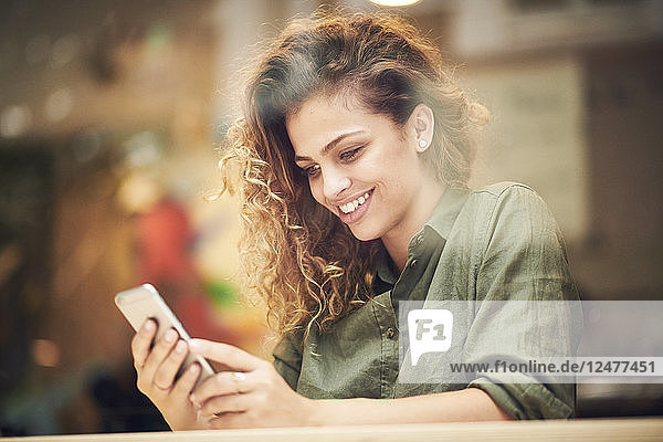 Young woman using smart phone behind cafe window