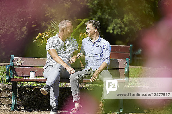 Gay couple sitting on park bench