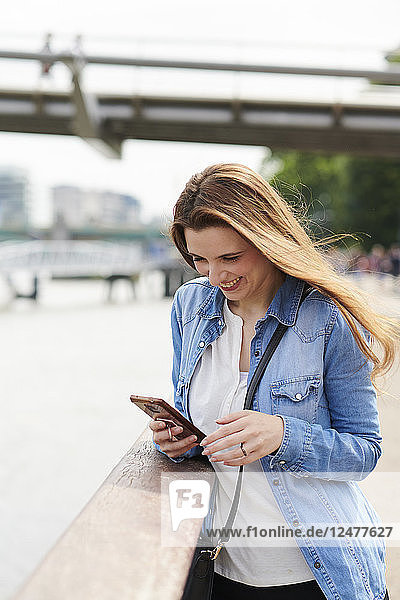 Mid adult woman smiling and using smart phone
