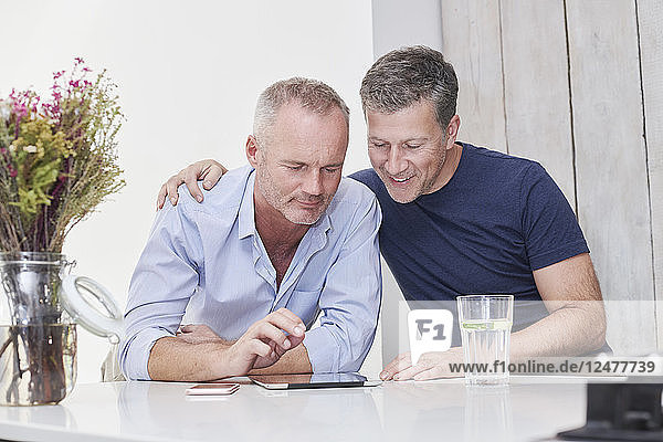 Gay couple using digital tablet in kitchen