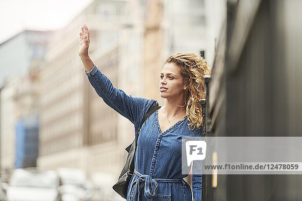 Young woman hailing taxi