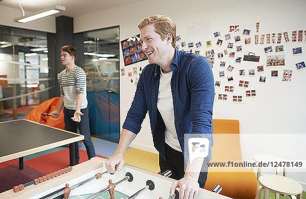 Lächelnder junger Geschäftsmann im Pausenraum seines Büros