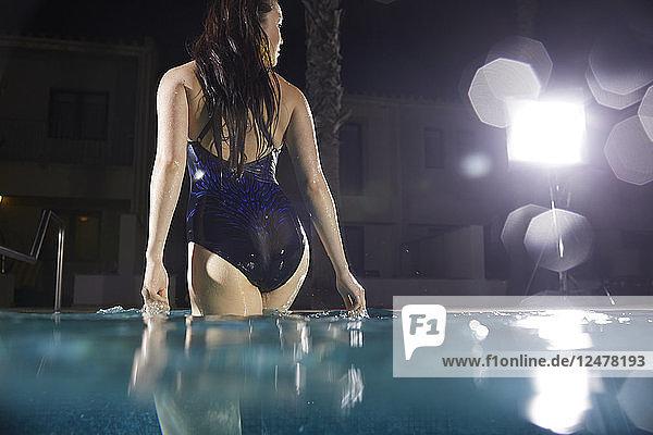 Woman wearing black swimsuit standing in swimming pool