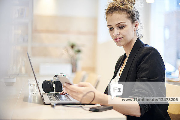 Young woman holding smart phone with laptop