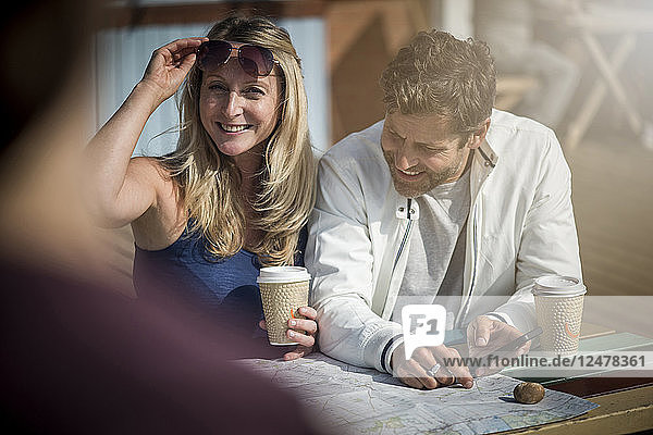 Couple with coffee and map