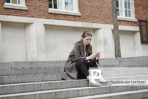 Woman holding smart phone on staircase
