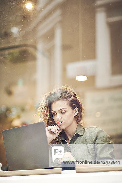 Young woman using laptop behind cafe window