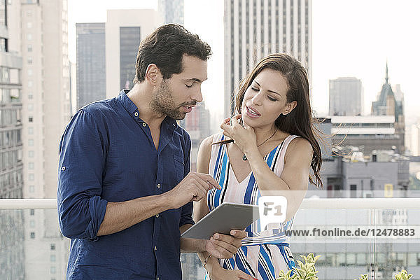 Young couple with tablet PC on balcony in New York City
