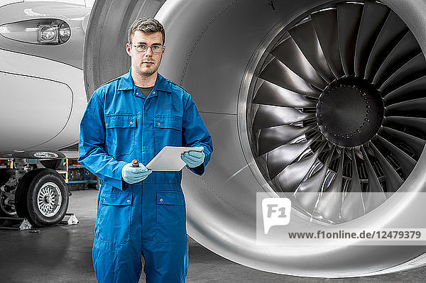 Young man holding digital tablet by airplane engine
