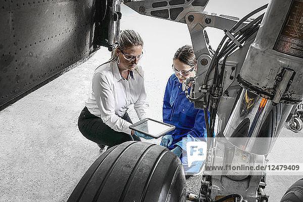 Women using digital tablet by airplane wheel
