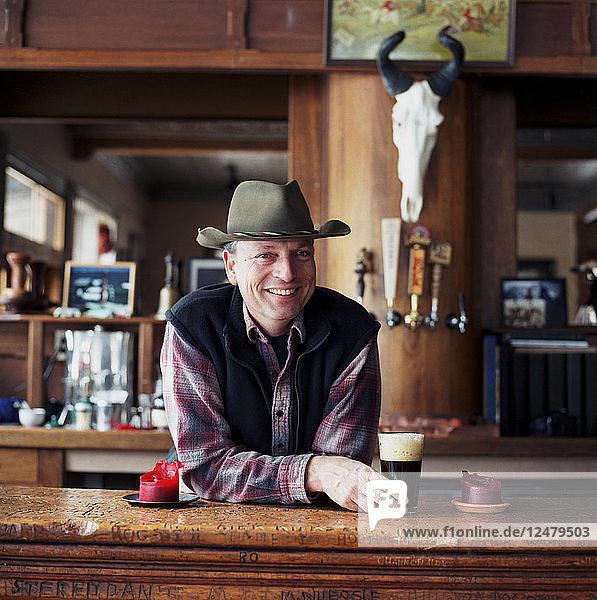 Mann mit Cowboyhut lächelt in einer Bar