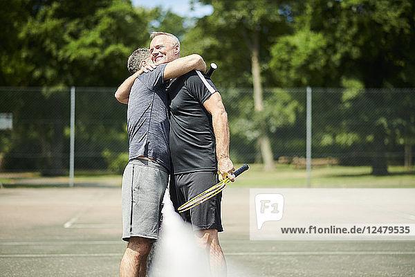 Mature couple hugging on tennis court