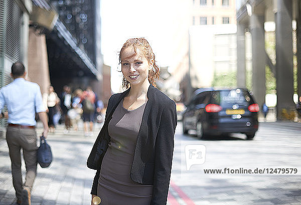 Portrait of young businesswoman on city street