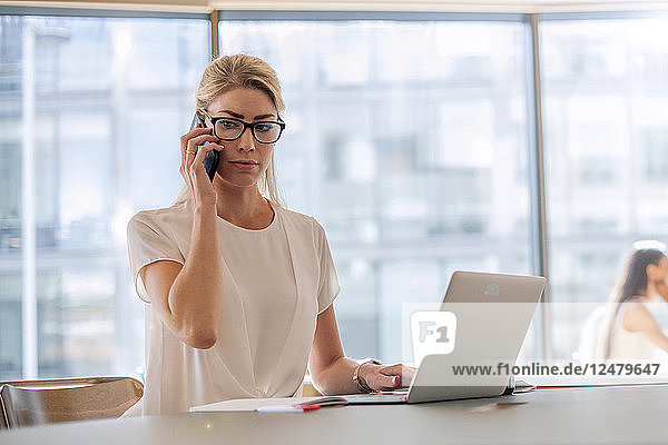 Businesswoman using laptop and note pad