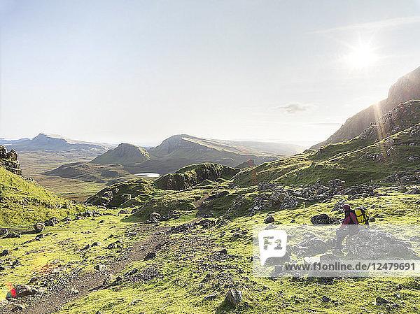 Hiker sitting on rock on hill