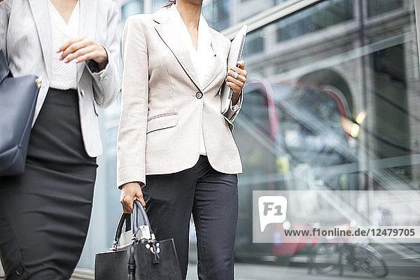 Businesswomen walking on sidewalk