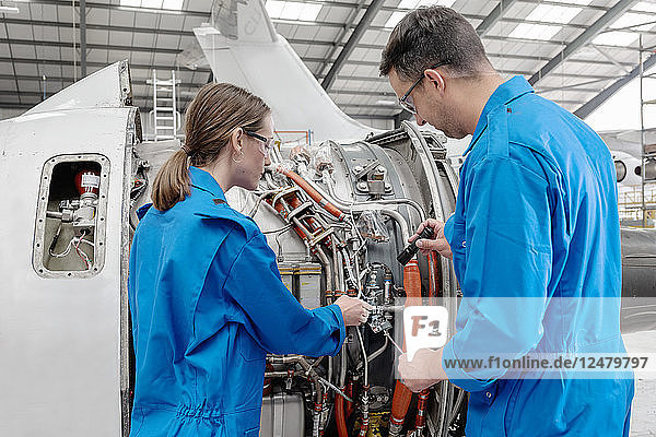 Man and woman working on airplane engine