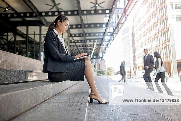 Businesswoman using smart phone and laptop on train platform