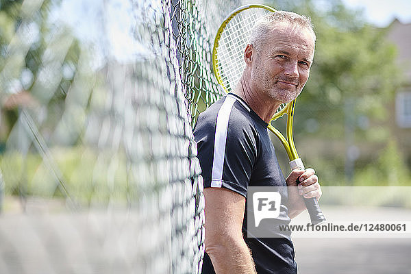 Mature man holding tennis racket leaning on fence