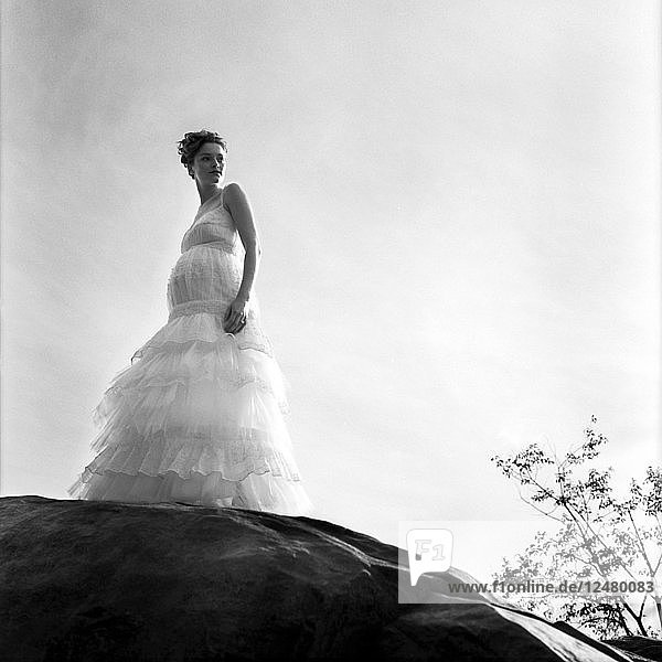Pregnant bride standing on rock