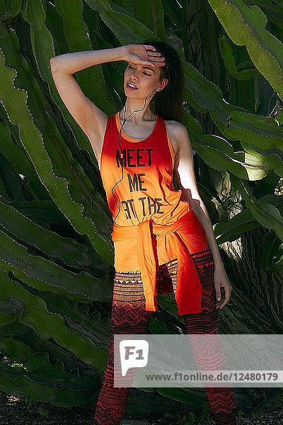 Junge Frau posiert neben einem Kaktus