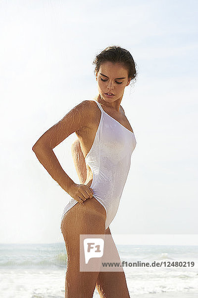 Young woman wearing white swimsuit showering on beach