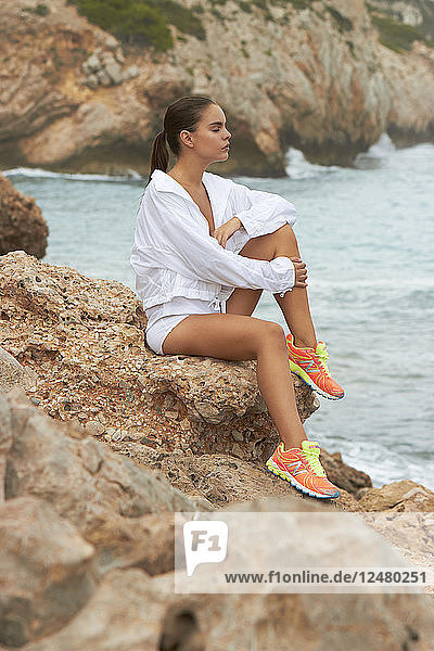 Young woman wearing jacket and trainers by sea