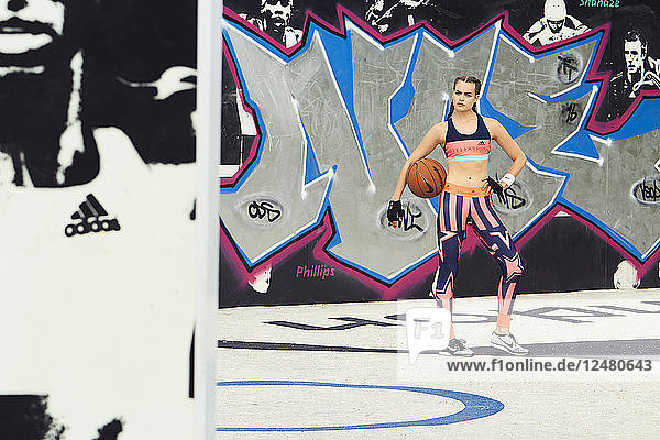 Young woman holding basketball by graffiti