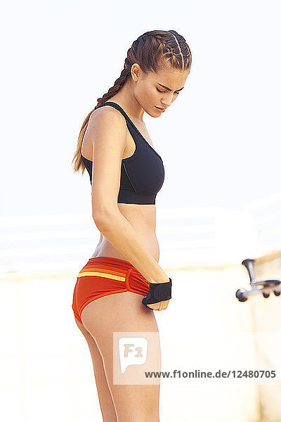 Young woman in sports bra at beach in Barcelona