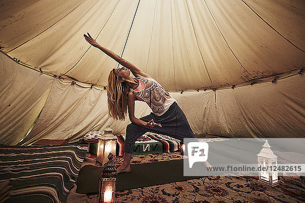 Young woman doing yoga in tent