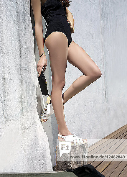 Legs of model posing against wall