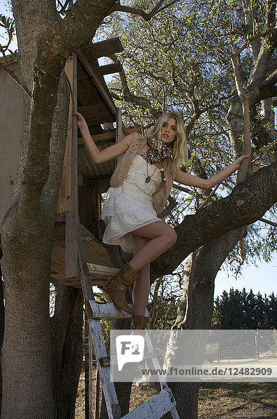 Young woman posing beside tree house