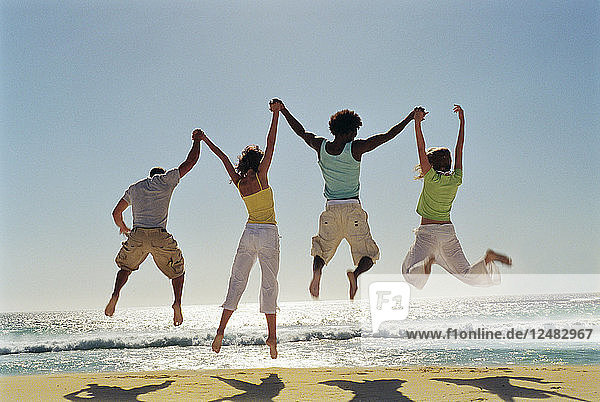 Friends jumping together on beach