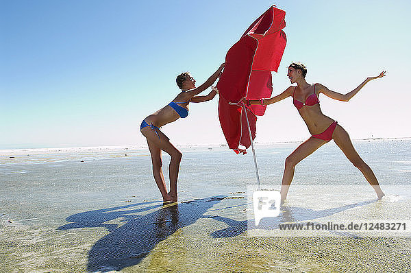 Women playing with umbrella on beach