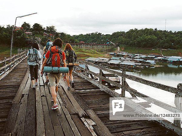 Friends walking on wooden bridge in Thailand